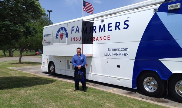 Agent standing in front of Farmers logo coach bus.