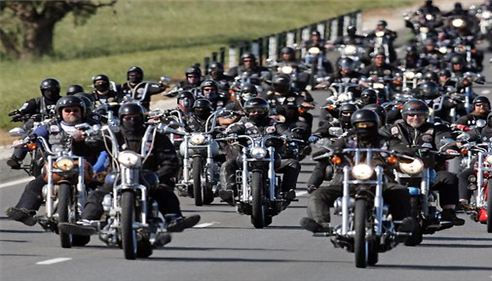 A large group of motorcyclists riding down open road.