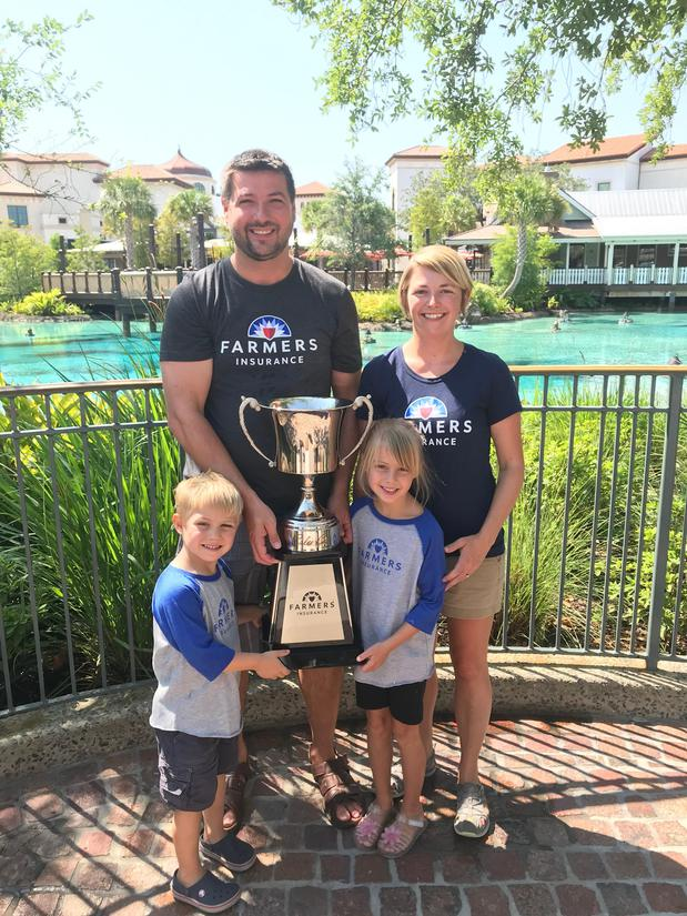 Family of four holding trophy.