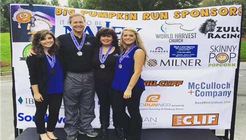 Agent Mark Lane with his family in front of a banner sponsoring the Pumpkin Run in Roswell.