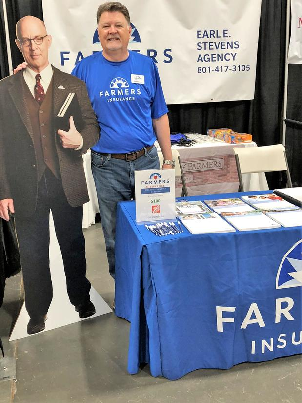 Agent standing at a Farmers booth with a cardboard cutout of Professor Burke