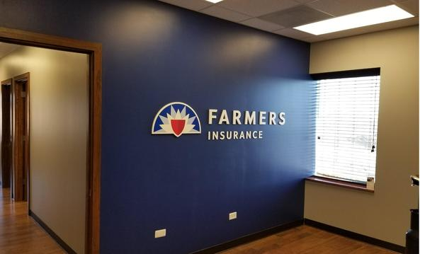 The Farmers Insurance logo on a blue wall inside of an office, with a window and hallway in view.