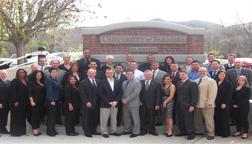 A large group of people standing in front of a Farmers University sign