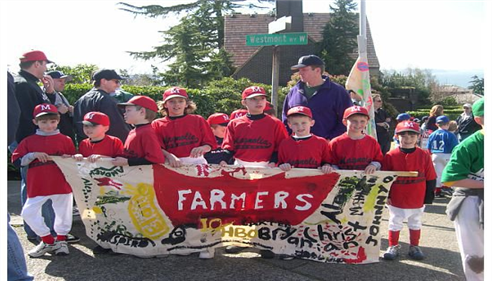 A little-league team hold up a Farmers Insurance banner and smile at the camera