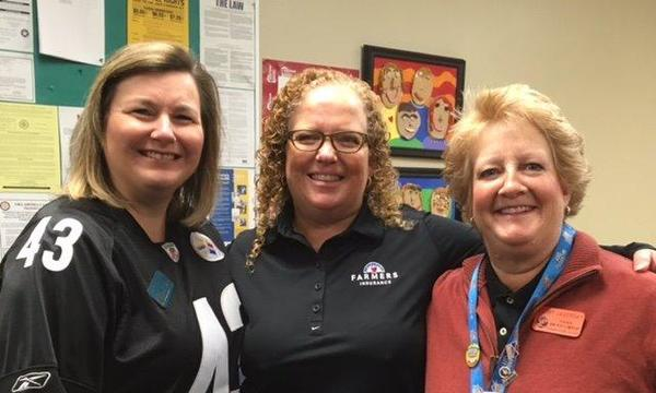 Agent Janna Lookabaugh with two female teachers inside a classroom of a local elementary school.