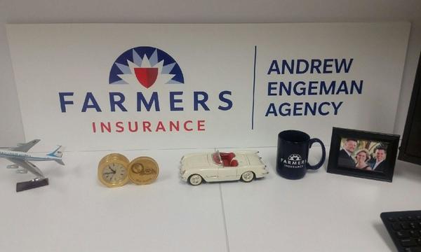 Farmers Insurance Andrew Engeman sign with a small figurines of an airplane, a time piece, a white car, a small cup and a frame of a photo.