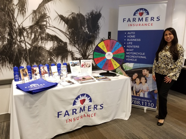Agent standing next to Farmers Insurance booth in front of some plants.
