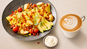 Omlette with avocado and tomatoes on a plate next to a cappuccino.