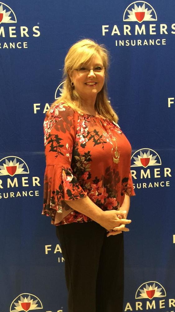 a woman standing in front of a farmers logo backdrop