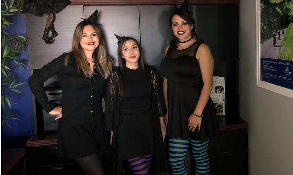 3 female staff members dressed as witches for Halloween.