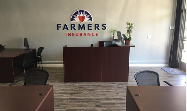 inside the office shows 3 desks with the Farmers Logo above the centered desk