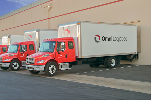 Three red and white trucks with Omni Logistics logos being loaded at freight forwarding distribution center dock doors