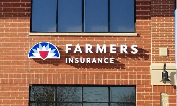 The Farmers Insurance logo on the outside of a brown brick building.