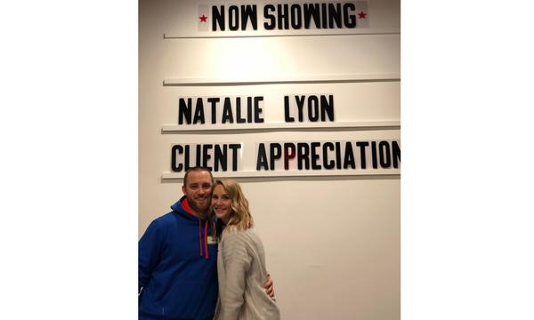 "Two people posing in front of wall with marquee that reads ""Natalie Lyon Client Appreciation"""