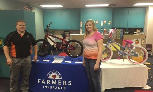 Agent Donald Zerr standing with a woman in front of a Farmers Insurance promotional table with a bicycle on top of it