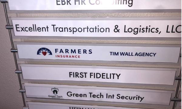 The business name card at the entrance of a building for Farmers Insurance Tim Wall Agency