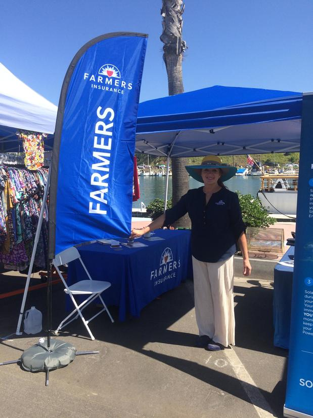 Laurie standing next to her Farmers booth at the Oceanside Harbor Fair