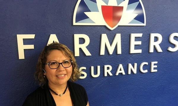 A woman standing in front of the Farmers Insurance logo.