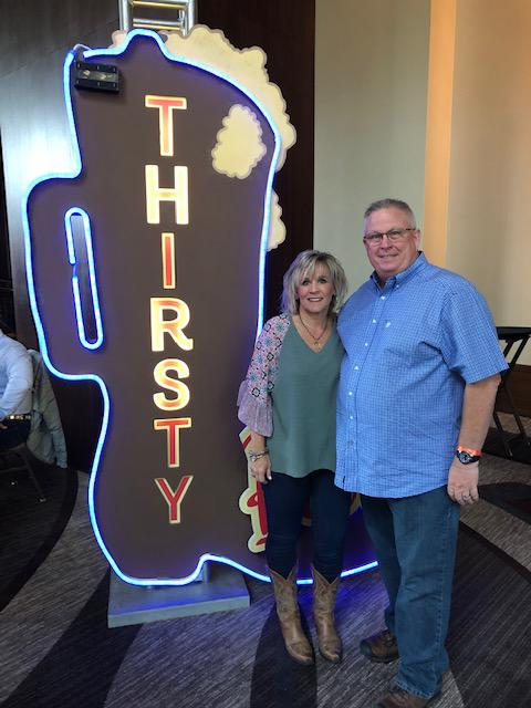 Man and woman standing next to a sign that says thirsty