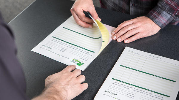 ncr carbonless forms being flipped through at the counter