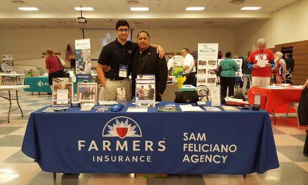 Agent standing with man behind a Farmers table at an event