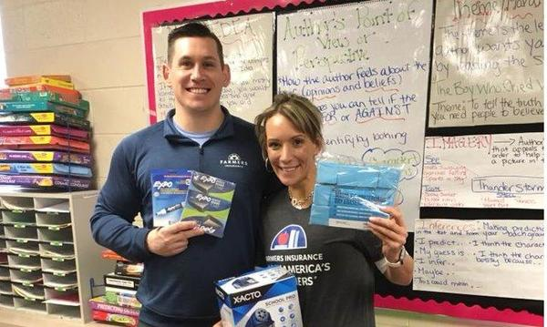 Agent posing with a teacher who is holding school supplies.