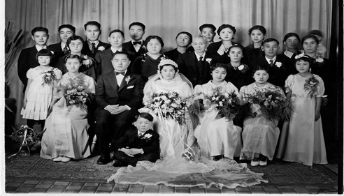A family of adults and children posing for a wedding photo.