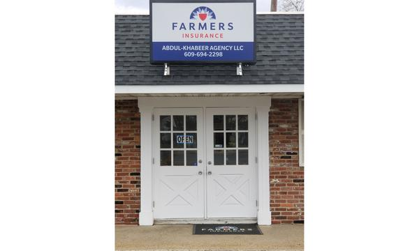 Storefront with large white doors and Farmers Sign above.
