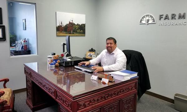 Agent Arnold Alaniz sitting behind his desk smiling.
