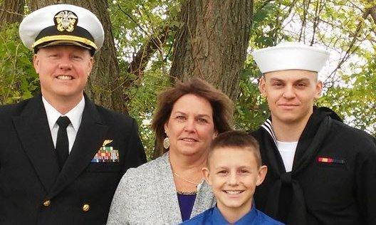 A family photo! Two men in uniform along with mom and another son