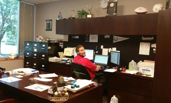 Agent Matt North in his office, working at his desk.