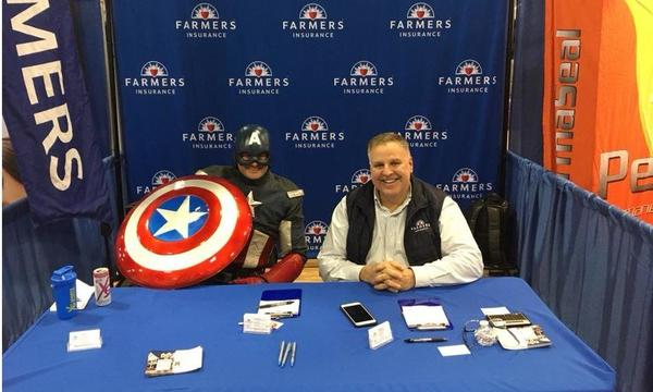 Male staff sitting with a man dressed in Captain America costume.