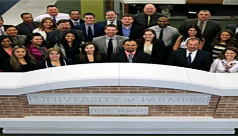 Group of people standing behind a Farmer University sign