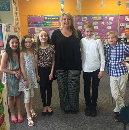 A teacher stands with five student in a classroom