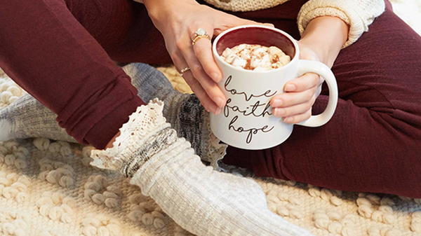 "A woman sits on a plush white carpet in comfortable cable knit socks, burgundy leggings and a waffle knit beige sweater, she is holding a mug that says ""Love, faith & hope"" in cursive."