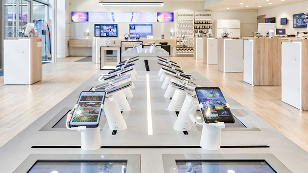 IPads and smart phones sit in white display stands on a long table inside a SFR showroom