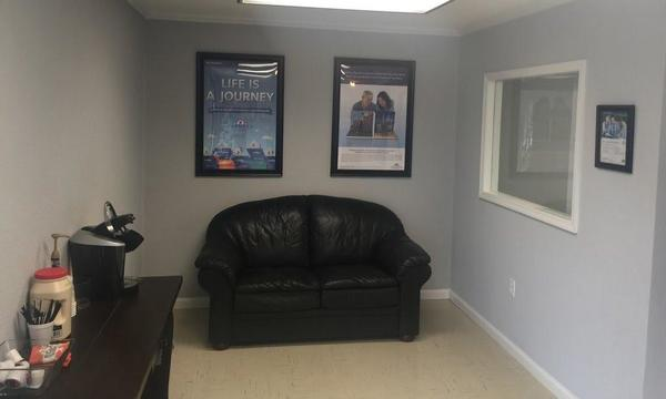 Photo of the agent's waiting area with a black couch.