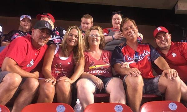 Group of 5, two women and 3 men wearing Cardinals gear at a game.