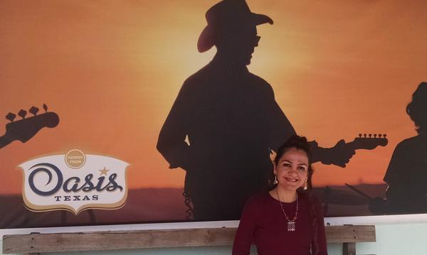 David Wylie Agency staff member Rusul standing in front of a tourism ad for Oasis Texas.