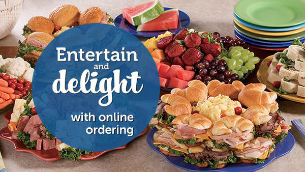 "Picture of sandwiches, fruits, meats, cheeses and vegetables on a table.  ""Entertain and delight with online ordering."""
