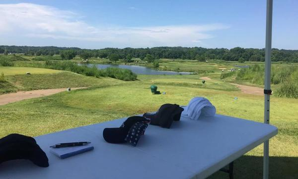 Table with 4 rows of hats, golf course and pond in the background