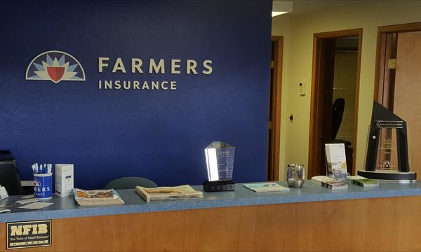 A photo of the front desk of the Steele Agency with the Farmers Logo on the wall.
