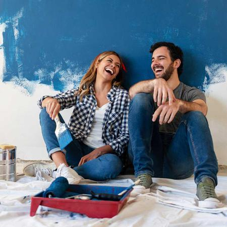 A couple laughs together while painting their wall