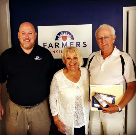 Three people posing in front of farmers logo