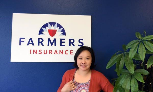 A woman poses in front of a blue wall and a Farmers Insurance logo next to a plant