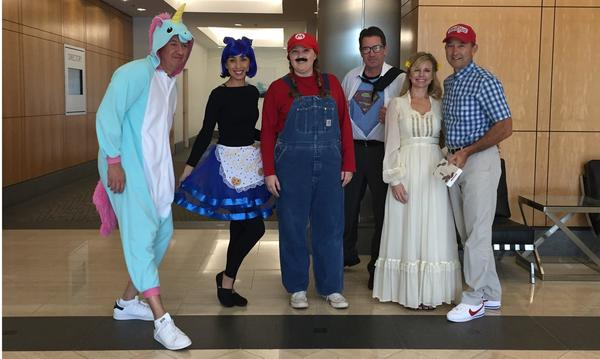 Group at agency standing in Halloween costumes