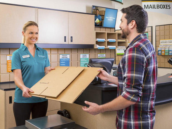 ups store associate handing male customer boxes