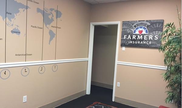 Photo of corner of the room. Map of the world on the left, Farmers logo on the right.
