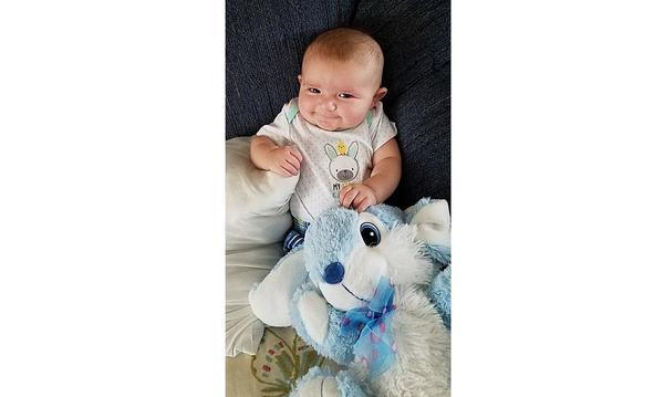 infant child holding a blue bunny