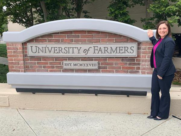 Agent posing outside of University of Farmers sign.